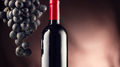 Wine. Bottle of red wine with ripe grapes over black background - PhotoDune Item for Sale