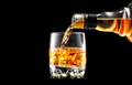 Whisky pouring from the bottle over black background. Whiskey on - PhotoDune Item for Sale