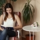 Young Beautiful Girl Reading a Book Sitting in a Chair A Woman Laughs at Reading a Book Positive - VideoHive Item for Sale