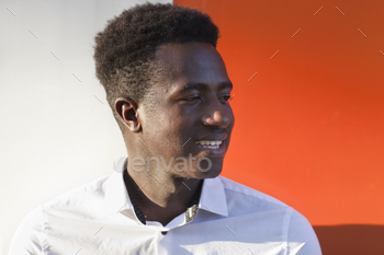 Handsome smiling young black man on orange and white divided background