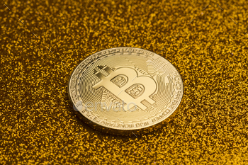 single bitcoin coin on golden glittering background