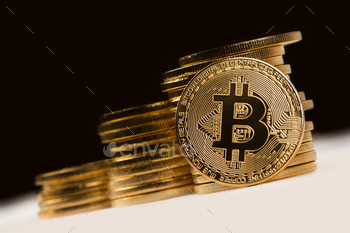 golden bitcoin in front of a pile of golden metallic coins on bl