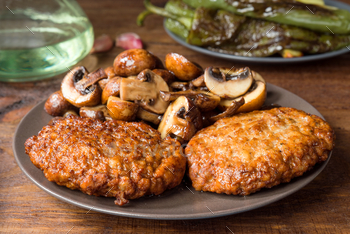 homemade burgers and mushrooms grilled on rustic wood