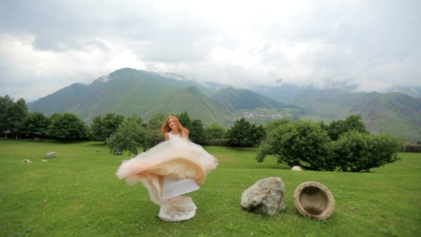 Beautiful Red-haired Bride Dancing Against the Background of Mountains