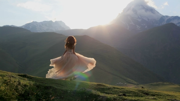 Beautiful Girl in a Chic Dress Dances in the Evening Against the Backdrop of the Mountains