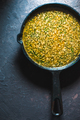 Yellow curry paste in a cast-iron frying pan on a blue background. Indian food - PhotoDune Item for Sale