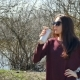 Young Brunette Woman in Sunglasses Drinking Some Beverage Using Thermo Cup on Lake Background - VideoHive Item for Sale
