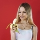 A Blonde Girl in a White Shirt Eats a Banana. Red Background. - VideoHive Item for Sale