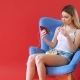 The Girl Sits in a Chair, Watching a Movie on the Phone and Eating Popcorn - VideoHive Item for Sale