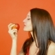 Smiling Woman with Healthy Teeth Eating Red Apple on Orange Background in Studio. Dieting Concept - VideoHive Item for Sale