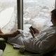 Young Man Texting on Smartphone Sitting on a Bed at Apartment Near Window with Great City View - VideoHive Item for Sale