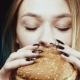 Delicious Fast Food. Aroma of Food. A Slender and Young Girl Holds a Hamburger. She Enjoys His Scent - VideoHive Item for Sale