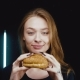 The Girl Is Holding a Hamburger. She Enjoys His Scent. - VideoHive Item for Sale
