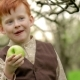 Red-haired Village Boy Eating a Fresh Apple in the Garden in - VideoHive Item for Sale