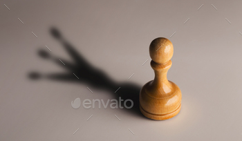 Wooden chess pawn with king shadow