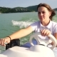 The Young Girl Steers The Motor Boat On The Lake - VideoHive Item for Sale