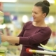 Young Mother with Her Daughter Choose Books in Supermarket - VideoHive Item for Sale