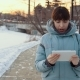 A Young Woman Uses a Digital Tablet Outdoors in Winter - VideoHive Item for Sale