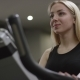 Blonde Girl Turns the Pedals on an Exercise Bike Watching the Time in New Gym - VideoHive Item for Sale