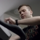 Handsome Guy Start Pedals on the New Exercise Bike and Track the Time in the New Gym - VideoHive Item for Sale