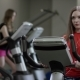 Nice Girl in Red Shirt Vigorously Works on Exercise Bike - VideoHive Item for Sale