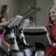 Nice Girl in Red Shirt Vigorously Works on Exercise Bike and Talks with Her Phone in the New Gym - VideoHive Item for Sale