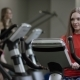 Lovely Girl in Red Shirt Vigorously Works on Exercise Bike and Just Working in the New Gym Against - VideoHive Item for Sale