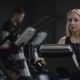 Lovely Girl in Blak Sport Wear Vigorously Works on Exercise Bike and Watchs Time with Her Wrist - VideoHive Item for Sale