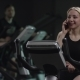 Nice Girl in Blak Sport Wear Vigorously Works on Exercise Bike and Talks with Her Phone in the New - VideoHive Item for Sale