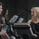 Nice Girl in Blak Sport Wear Vigorously Works on Exercise Bike and Guy Comes To Meet and To Ask Her - VideoHive Item for Sale