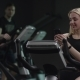 Nice Girl in Blak Sport Wear Vigorously Works on Exercise Bike and Texting Message in Chat with Her - VideoHive Item for Sale