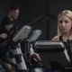 Pretty Girl in Blak Sport Wear Vigorously Works on Exercise Bike and Watchs Time with Her Wrist - VideoHive Item for Sale