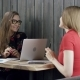 Two Young Business Women Are Sitting in Cafe with a Laptop - VideoHive Item for Sale