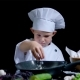 Little Boy Is Adding a Salt To the Dish, Wearing Chefs Suit and Cap - VideoHive Item for Sale
