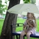 A Little Girl with a Toy Hare Sits on a Bench Under an Umbrella. - VideoHive Item for Sale