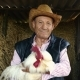 An Elderly Farmer in a Straw Hat Is Holding a Live White Rooster. Portrait of a Man with a White - VideoHive Item for Sale