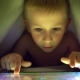 Young Blond Boy Under Covers Playing on Tablet a Computer Game. - VideoHive Item for Sale