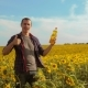 Man Farmer Hand Hold Bottle of Sunflower Oil the Field at Sunset - VideoHive Item for Sale