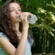 Outdoors Portrait of Young Brunette Girl with Curly Hair Is Drinking Mineral Water on Green Trees - VideoHive Item for Sale