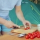 A Woman Is Cutting a Cherry Tomato with a Knife for a Salad on a Picnic - VideoHive Item for Sale