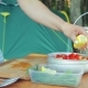 A Young Woman Squeezes Lemon Juice Into a Bowl with a Salad on a Picnic - VideoHive Item for Sale
