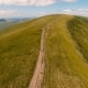 Aerial Shot of a Carpathian Range with a Country Lane with Three People in Summer - VideoHive Item for Sale