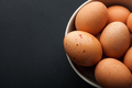 closeup brown eggs in bowl isolated on dark background - PhotoDune Item for Sale