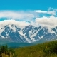 . Clouds Cover the Snow-covered Mountains in the Background. Shrubs Are Shaking in the Wind in the - VideoHive Item for Sale