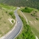 Aerial View of Cars and Bikes Traffic at Road in Mountains Above Valley - VideoHive Item for Sale