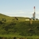 Green Hills Covered with Grass and Pumpjack Near High Tower - VideoHive Item for Sale