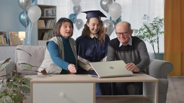 Family with Graduate Celebrating End of School Year Online and Preparing for Graduation Ceremony Via