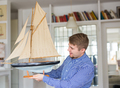 Hobby, collecting, ship and people concept - handsome man holding layout of a sailboat - PhotoDune Item for Sale