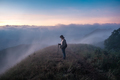 Girl standing on top of the mountain surrounded by fog - PhotoDune Item for Sale