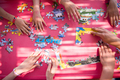 top view of kids hands playing with puzzles - PhotoDune Item for Sale